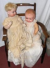 An old large German bisque head doll with glass eyes and open mouth, having