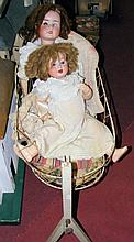 An old German bisque head doll with glass eyes and open mouth, having compo