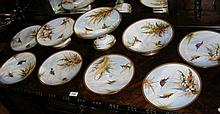 A decorative antique hand painted dessert service, including comports and plates with exotic bird and flower scenes