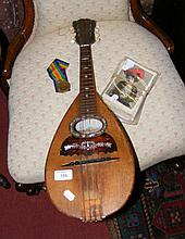 An old mandolin, together with collectable postcards and a medal