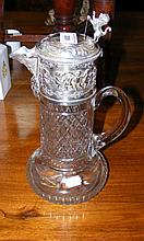 A 30cm high claret jug with silver plated lid