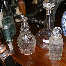 Two silver top decanters and one other