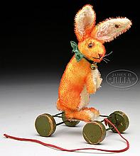 BRIGHT ORANGE MOHAIR STEIFF RABBIT WITH BUTTON ON WOODEN ECCENTRIC WHEELS.