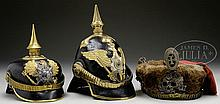 LOT OF THREE OFFICER HELMETS WITH ADDED REPRODUCTION PARTS.