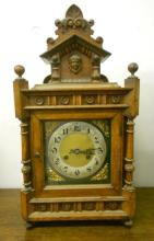 Golden Oak 2 Train Mantel Clock, silvered chapter ring, Arab numerals, brass centre with flower spandrels, architectural case, on 4 turned supports, turned columns, top of case surmounted with architectural & figural decoration, approx. 21