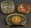 Three (3) Miniature Bejeweled Brass Mounted Tabletop Items. 1 Circular Dish. Measures 2-1/4 Inches Tall by 2-3/4 Inches Wide. Very Good Condition. 1 Oval Hand Painted Porcelain Footed Tray with a Portrait of P. Paul Rubens. Very Good Condition.