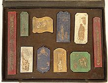 Early 20th Century Chinese Boxed Set of Ten (10) Molded Pottery Inkstones with Parcel Gilt Accents. Each Stone with Molded Design and Calligraphy, Box with Calligraphy and Seal Mark. Rubbing to Gilt, Box Damp Stained Otherwise Good Condition. Box