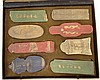 Early 20th Century Chinese Boxed Set of Eight (8) Molded Pottery Inkstones with Parcel Gilt Accents. Each Stone with Molded Design and Calligraphy, Box with Calligraphy and Seal Mark. Rubbing to Gilt, Box Damp Stained Otherwise Good Condition. Box