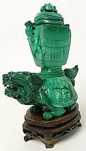 Chinese Carved Malachite Tortoise with Covered Urn on Carved Wood Base. Unsigned. Good Condition or Better. Measures 6-3/8 Inches Tall and 5-1/2 Inches Wide. Proceeds of the sale of this item to benefit the Leidesdorf Foundation, West Palm Beach,