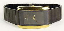 Man's Vintage Movado Blackened Stainless Steel and Gold Tone Quartz Movement Watch. Signed. Minor Surface Wear from Normal Use. Watch Appears to be Running. The Gallery does not Warranty the Running Condition of Watches. Case Measures 41 x 19mm.