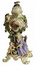 19th Century Meissen Porcelain Figural Potpourri Urn. The Body Mounted with a Climbing Monkey on Grapevines, a Putto and Maiden Flanking a Basket of Grapes. Marked with Blue Underglaze Crossed Swords Mark. Old Restoration to Bird Finial and Some