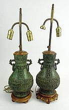 Pair Chinese Archaistic Bronze Vases Mounted as Lamps. Pear Shape with Twin Dog and Ring Handles, Molded with Characters and Geometric Forms with Wooden Base & Cap. Sliding Tube to adjust Lamp Shade. Very Good Condition. Vases Measure 12 Inches Tall