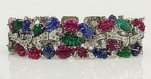Very fine quality lady's Cartier style approx. 82.0 carat carved sapphire, ruby emerald, round cut diamond and 18 karat white gold tutti-frutti bracelet. Diamonds E-F color, VS clarity. Unsigned. Very good condition. Measures 7-3/8 inches long and 1
