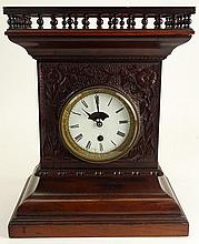 Late 19th Century Carved Wood Mantel Clock. Wood Case With Gallery Top. Porcelain Dial. Works Signed Boston Clock Company. Dial Has Cracks, Appears to be running although The gallery does not warranty the running condition of Clocks. Measures 14-1/2