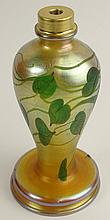 Antique Tiffany Favrile Iridescent Glass Lamp Base. Gold Luster Decorated with Leaf and Vine Motif. Signed L.C.Tiffany Favrile. Extremely tiny chip on bottom underside rim and internal crack on base. Measures 9 Inches not including Hardware. Shipping