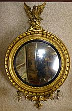 Early 19th Century American Federal Carved and Gilt Wood Convex Mirror With Figural Eagle Finial. 2 Lights with Glass and Prismed Bobeches. Unsigned. Some Losses (prisms) Age Splits and Restoration. Measures 56 Inches Tall, 34 Inches Width. We will
