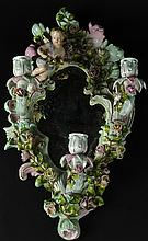 Antique Meissen Style Figural Porcelain Three (3) Light Mirrored Sconce. Decorated with Putti amidst Flowers. Unsigned. Minor Typical Losses to Petal and Leaves or in Good Condition. Measures 19 Inches Height by 10-12 Inches Wide. Shipping $135.00