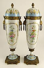 Pair 19th Century Sevres Bronze Mounted Hand Painted Porcelain Covered Urns. Figural Rams Head Ring Handles. Signed with Sevres Mark. The Top Rim Affixed to Lid on One Urn, The other is Affixed to Urn or in Good Condition. Measures 18-1/2 Inches