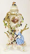 19th Century Meissen Porcelain Figural Potpourri Urn. The Body Mounted with a Climbing Monkey on Grapevines, a Putto and Maiden Flanking a Basket of Grapes. Marked with Blue Underglaze Crossed Swords Mark. Typical Minor Losses Consistent with age.
