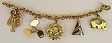 Lady's vintage 18 karat yellow gold charm bracelet with four 14 karat yellow gold charms and one 18 karat yellow gold charm. Propeller charm set with approx. .45 carat round cut diamond, G-H color, SI1 clarity. Lobster charm set with small round cut