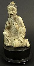 Chinese Carved Ivory Figure of a Elderly Man Kneeling. Nicely Detailed. Mounted on a Hardwood Base. Signed on Back with Red Chinese Characters. Very Good Condition. Measures 4-1/4 Inches Tall by 3 Inches Across and 1-3/4 Inches Wide. Base Measures