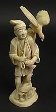 Chinese Ivory Carved Jointed Figure of a Man Holding a Fish with a Bird on His Back. Very Good Condition. Measures 9 Inches Tall by 4 Inches Across and 3-1/2 Inches Wide. This item will only be shipped domestically and was legally imported into the