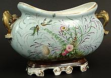 19/20th Century Continental Painted and Gilt Porcelain Cachepot with Gilt Dolphin Handles and Bird and Flower Decoration. Impressed Number 58 to Base Otherwise Unsigned. Rubbing to Gilt Decoration, Small Firing Flaws Otherwise Good Condition.