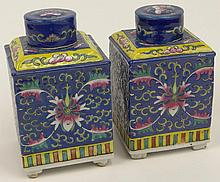 Pair of 20th Century Chinese Porcelain Tea Caddies with Covers. Each Decorated with Floras in Blue, Yellow, Red and Green. Marked China with Characters on the Base. Very Good Condition. Each Measures 6 Inches Tall by 3-5/8 Inches Square. Shipping