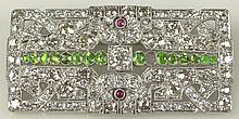 Lady's Art Deco Round Brilliant Cut Diamond, Demantoid Garnet, Ruby and Platinum Brooch. Garnets with Vivid Saturation of Green Color. Diamonds F-G Color, VS1-VS2 Clarity. Unsigned. Missing One (1) Garnet Otherwise Good Condition. Measures 1 Inch