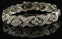 Tiffany Style Platinum and Diamond Elegant Braided Bracelet. Set Throughout with 11 Carats Round Brilliant Diamonds of E-F Color and VS1-VS2 Clarity. Signed 10% IRID. Excellent Condition. Measures 7 Inches Length, 1/2 Inch Width and weighs Approx.