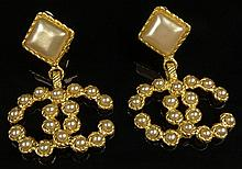Pair Chanel Faux Pearl Gold Tone Logo Drop Earrings. Clip On Style. Signed on Back Chanel, Made In France 2,8. Very Good Condition. Measures 2-1/2 Inches Length, 1-3/4 Inches Width. Domestic Shipping $28.00