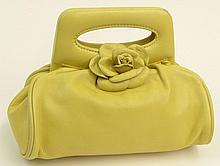 Chanel Yellow Leather Handbag with Camellia. Signed and Carte D'Authenticite #8672659. Slight Wear, Small Scuff to Handle Otherwise Good Condition. Measures 6-3/4 Inches Tall and 8-3/4 Inches Wide. Shipping $34.00