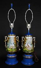 Pair of 19th Century Old Paris Porcelain Ring Handled Vase/Lamps. Currently Drilled and Converted into Lamps. Each Finely Detailed with Hand Painted Scenes of Birds in a Garden Setting Overlooking Fountains, Statuary and Water that Completely
