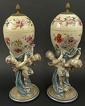 Pair of Early 20th Century French Covered Faience Urns with Figural Putti Pedestal Bases, Gilt Bronze Finials and later painted floral decoration. Urns Signed HC to Bases, Floral decoration artist signed Guillaume. Rubbing Otherwise Good Condition or