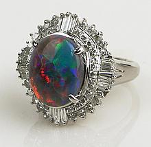 Very Fine 4.16 Carat Black Opal, 1.08 Carat Round Brilliant Cut and Tapered Baguette Diamond and Platinum Ring. Opal with Very Good Display of Red, Green and Blue Color. Diamonds E-F Color, VS1-VS2 Clarity. Signed P900. Very Good Condition. Ring Size