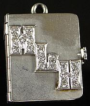 Diamond and 14 Karat White Gold Book Locket Charm or Possibly Pendant. Initials HLH Spelled out in Diamonds on Cover of Book, which Opens to a Miniature Photograph and Rear Page Candle Figure in Diamonds. Overall Good Condition, Scratched to the