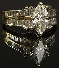 Lady's 14 Kt Yellow Gold and Diamond Engagement Ring. Set in the Center with a Marquis Cut Diamond Weighing Approx 1.5 Carats K-l Color VS2 Clarity. Ring is Further Accented with Baguette and Tapered Baguette Diamonds. Weighing Approx. 1.5 Carats