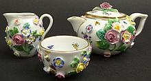 19th Century Miniature Meissen Floral Encrusted Teapot, Cream Pitcher and Open Sugar Three (3) Piece Tea Set. Signed Under Glaze Crossed Swords. Usual Losses or else Good to Very Good Condition. Teapot Measures 2-1/4 Inches Tall and 4 Inches Long.