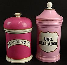 Two (2) 19/20th Century Painted and Gilt Porcelain Covered Apothecary Jars. Unsigned. Hairline Cracks and Chip to One Lid, Rubbing to Gilt Decoration Otherwise Good Condition. Taller Measures 13-1/2 Inches Tall and 6 Inches Wide. Shipping $125.00