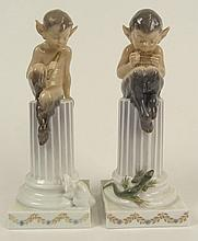 Vintage Royal Copenhagen Porcelain Satyr Figurines. Both Atop Columns. One With Lizard, One with Rabbit. Signed with Royal Copenhagen Backstamp and Wave Mark. The Rabbit with Losses to ears or in Good Condition. Measures 8-1/2 Inches Tall. Shipping