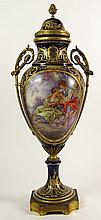 Large 19/20th Century Hand Painted Bronze Mounted Sevres Urn with Lid. The Front Panel Depicting a Hand Painted Romantic Scene Signed Bombois. Ornate Gilt Decoration Throughout on Cobalt Ground. Wreath Handles. Unsigned. Light Scratches and Wear to