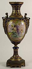 Large 19/20th Century Hand Painted Bronze Mounted Sevres Urn. The Panels Depicting Hand Painted Cherubic Scenes. Ornate Gilt Decoration Throughout on Cobalt Ground. Figural Handles. Signed with Painted Sevres Mark. Wear to Gilt Décor or in Good