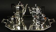 Christofle Five (5) Piece Silver Plate Coffee Service. Ebonized Wood Handles. This Lot Includes, Coffee pot, Tea Pot, Covered Sugar Bowl, Cream Pitcher and Tray. All Signed Christofle France. Light Surface Scratches on Tray, Sugar Bowl With Dings or