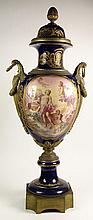 Monumental 19/20th Century Hand Painted Bronze Mounted Sevres Urn. The Panels Depicting Hand Painted Cherubic Scenes. Ornate Gilt Decoration Throughout on Cobalt Ground. Wreath Handles. Signed with Intertwined L Mark. Bolt missing from One Handle,