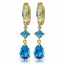 14K. GOLD HUGGIE EARRING WITH DANGLING BLUE TOPAZ