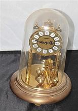 Table pendulum clock under plastic bonnet