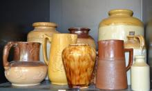 SHELF OF STUDIO POTTERY VASES AND DECANTERS AND A BURSLEM JUG, 19TH CENTURY