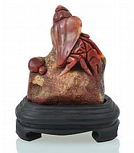 A CHINESE RED STONE CARVING ON STAND