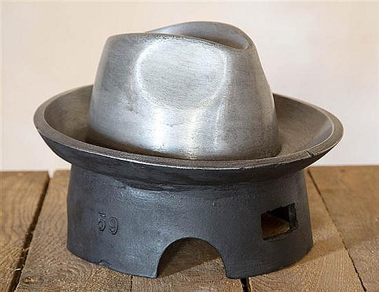 A CAST ALUMINIUM HAT BLOCK