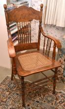 A PRESSED BACK OAK CHAIR WITH A CANE INSET SEAT